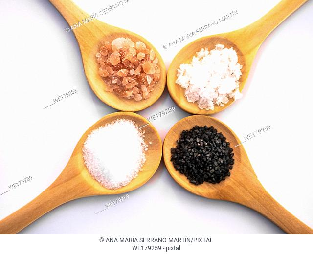Wooden spoons with himalayan salt, black hawaii salt, common salt and salt flakes on a white background