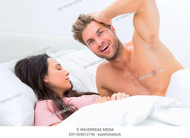Shirtless man posing next to his sleeping partner