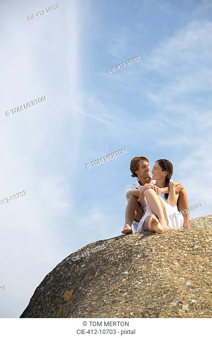 Couple relaxing on rock formation