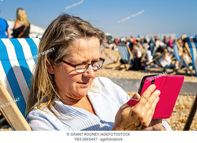 A Middle Aged Female Looking At Her Smartphone, Brighton Beach, Brighton, Sussex, UK
