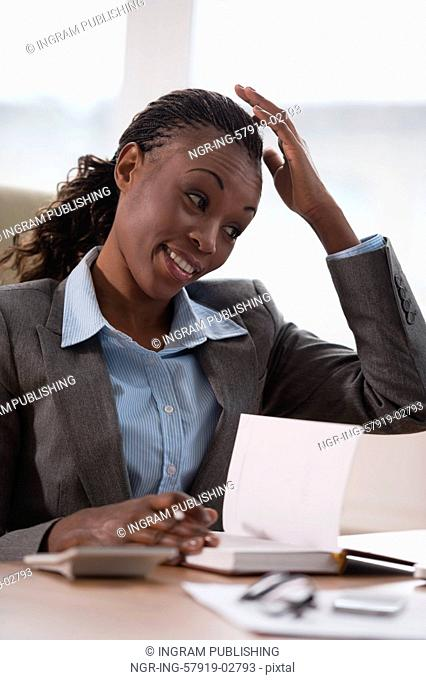 Young businesswoman sitting at workplace and writing numbers in notebook after calculating budget