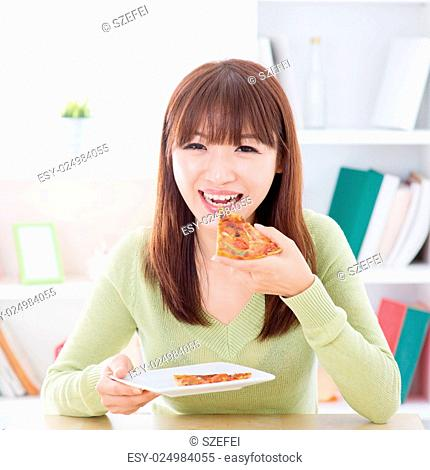 Asian woman eating pizza at home. Female living lifestyle indoors