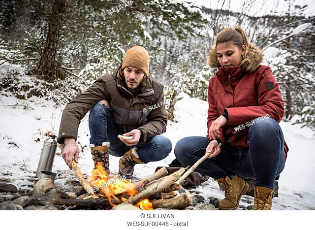 Couple on a trip in winter having a break at camp fire