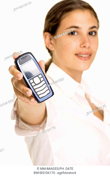 An attractive young woman holds up a cellphone