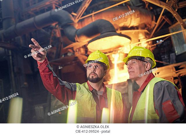 Steelworkers talking, pointing and looking away in steel mill