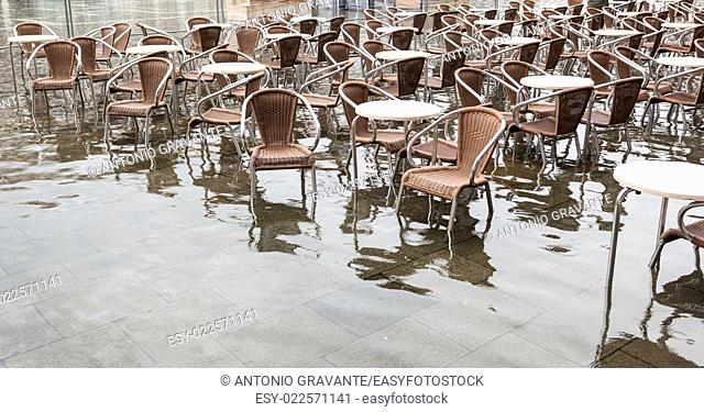 Tables and chairs with high water in Saint Mark's square, Venice, Italy