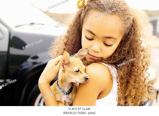 Mixed race girl petting dog outdoors