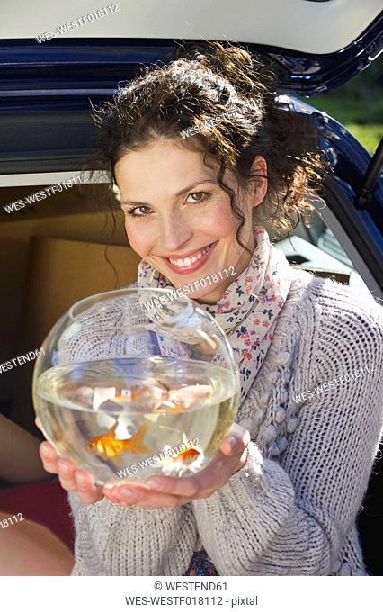 Germany, Bavaria, Grobenzell, Mid adult woman holding goldfish bowl, smiling, portrait