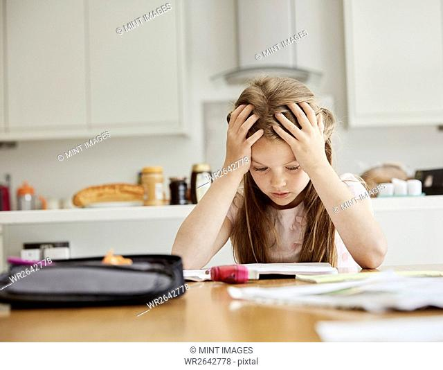 A girl sitting at a table with her hands on her head, looking at her homework
