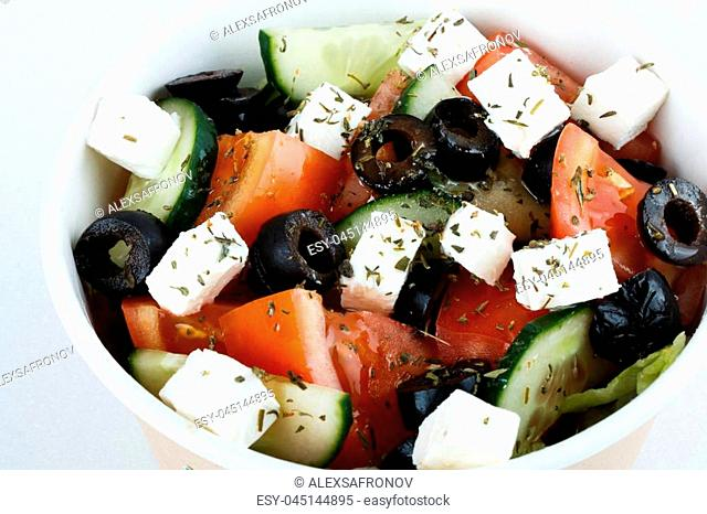 Greek salad with fresh vegetables, feta cheese and black olives on a white background. Top view. Free space for your text. isolated