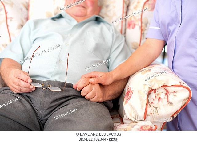Close up of Caucasian nurse holding hand of patient