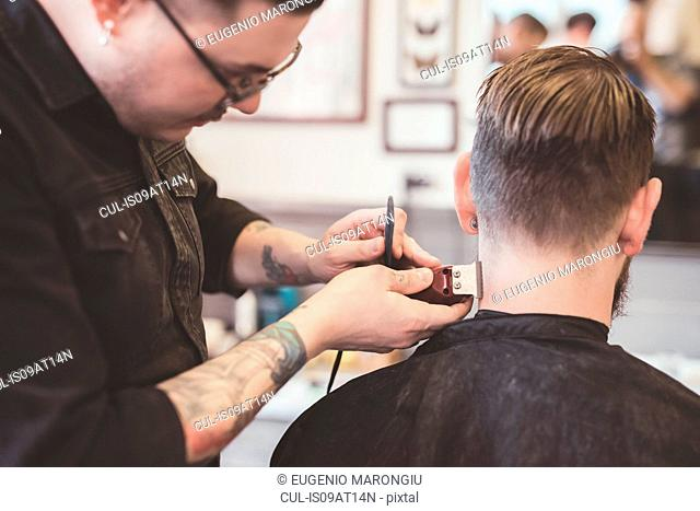 Barber using clippers on clients neck in barber shop
