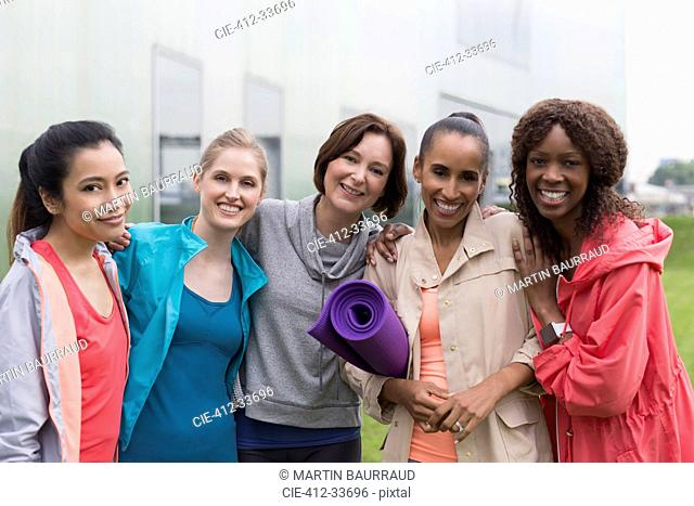 Portrait smiling women friends with yoga mat