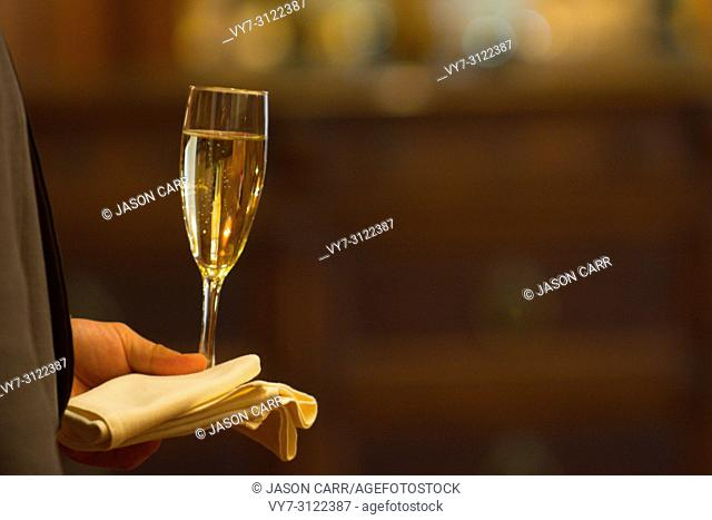 Champagne Glass on the hand of waiter. 3 seconds before starting toasting