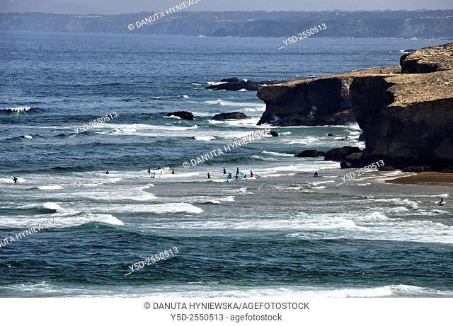 Europe, Portugal, Algarve, Faro district, Azjezur, Costa Vicentina, Monte Clérigo beach, Praia do Monte Clérigo, surfers in waters of Atlantic Ocean