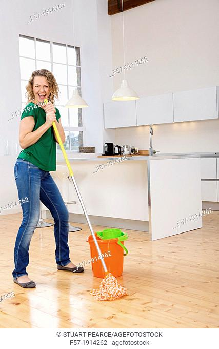 Woman singing while mopping her kitchen floor