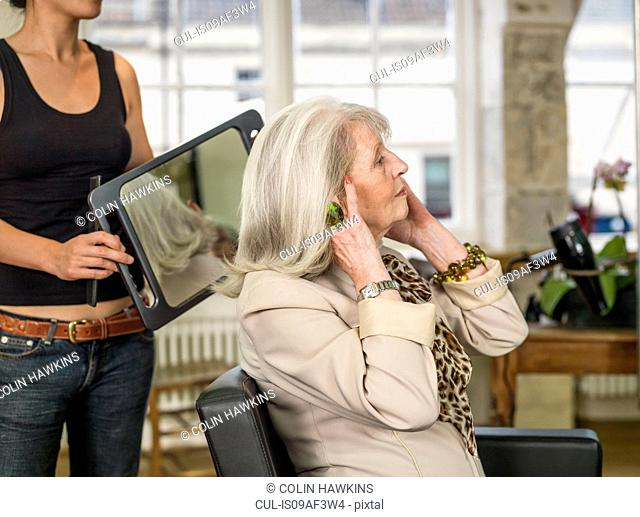 Senior woman admiring hairstyle at hairdressers
