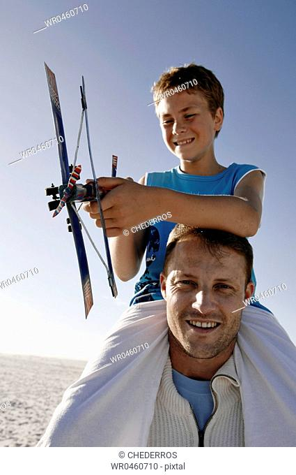 Portrait of a mid adult man carrying his son on his shoulders and smiling