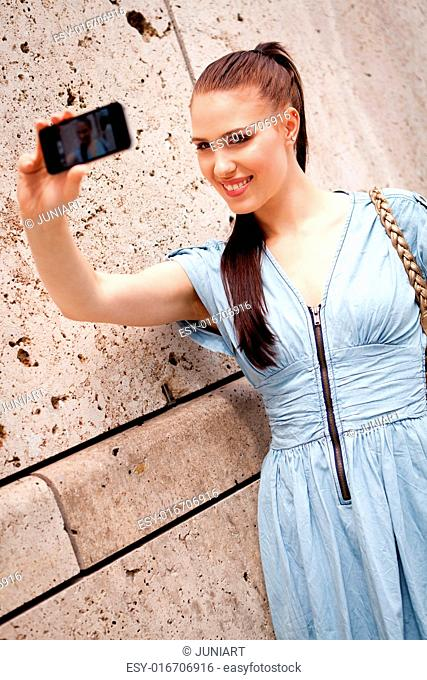 attractive young woman with smartphone camera photos outdoor in summer