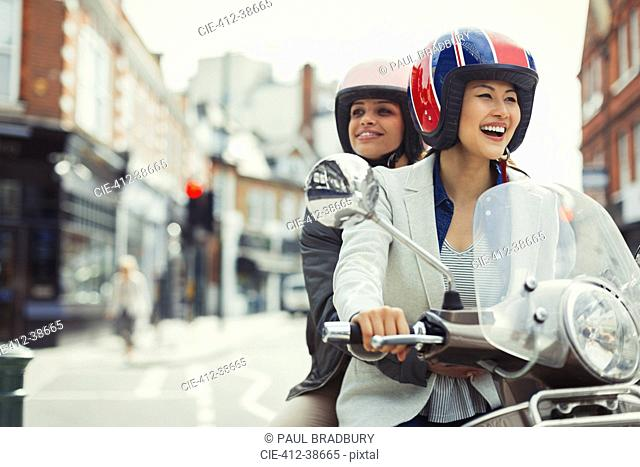 Smiling young women friends wearing helmets and riding motor scooter on urban street