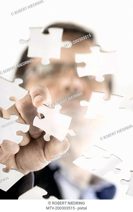Businessman arranging jigsaw puzzle pieces, Bavaria, Germany