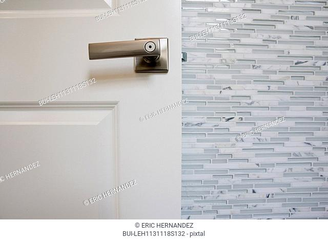 Detail shot of a white door with designed wall in the bathroom at home; Irvine; California; USA