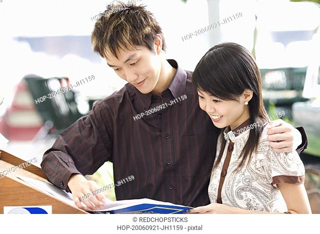Close-up of a young couple reading a book and smiling