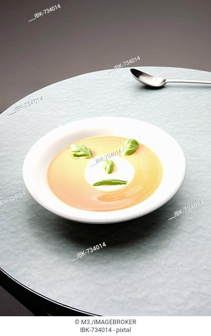 Bowl of tomato soup garnished with cream and basil in the shape of a face
