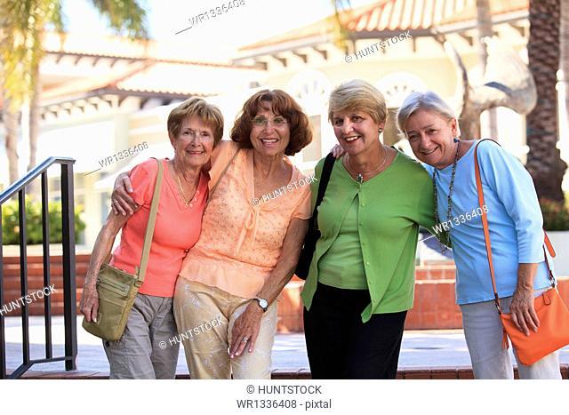 Four senior friends smiling