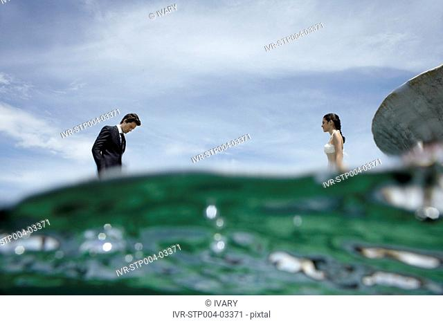 A businessman and a young woman facing one another