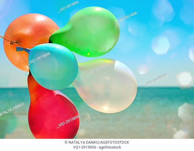 Multicolored balloons flying against the sea in the sun