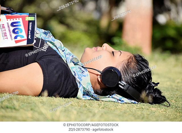 Young girl student lying on grass and listening music on headphone outside in the garden, Pune, Maharashtra