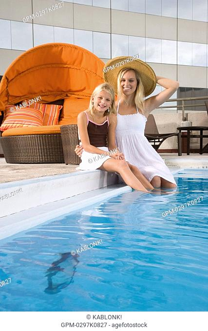 Mother and daughter relaxing at swimming pool on rooftop terrace in city