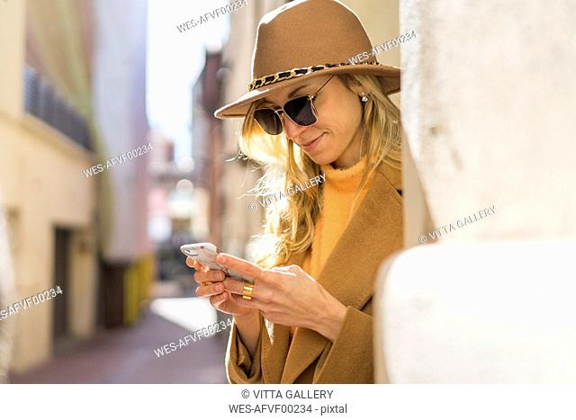 Fashionable young woman in a lane using cell phone