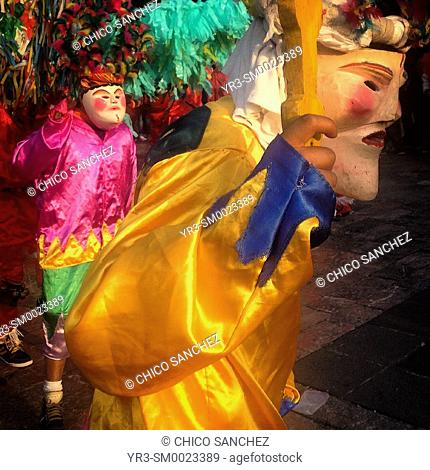 Men wearing masks and dressed in bright colors dance during the annual pilgrimage to the Our Lady of Guadalupe basilica in Mexico City, Mexico