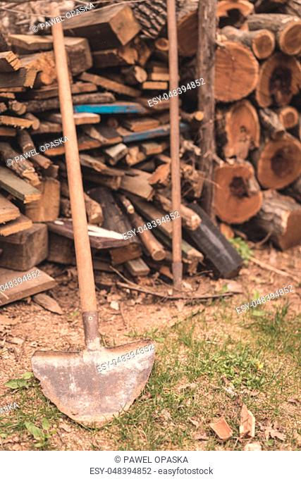 Old and rusted garden shovel in front of a firewood in a garden