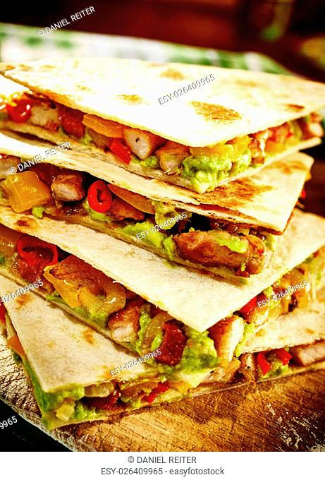 Stack of four quesadillas cooked with turkey or pork, guacamole, tomatoes and red peppers