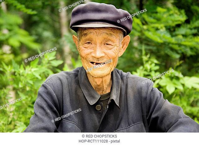 Portrait of a senior man smiling, Zhigou, Shandong Province, China