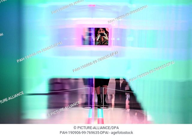06 September 2019, Berlin: A young woman photographs an installation on the first public day at the IFA technology trade fair