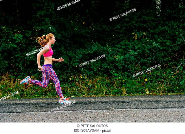 Teenage girl running along rural road