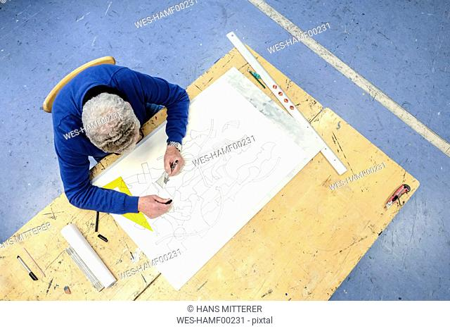 Top view of artist drawing in his studio