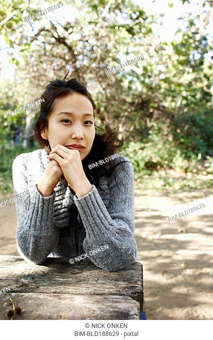 Asian woman sitting at picnic bench