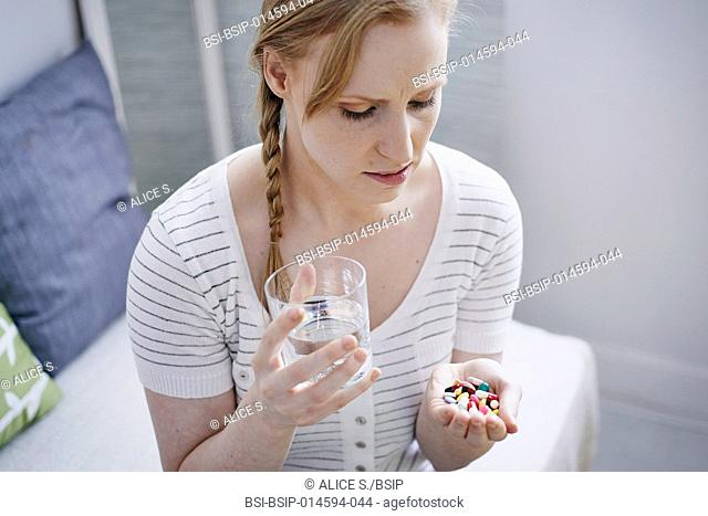 Woman holding a lot of pills