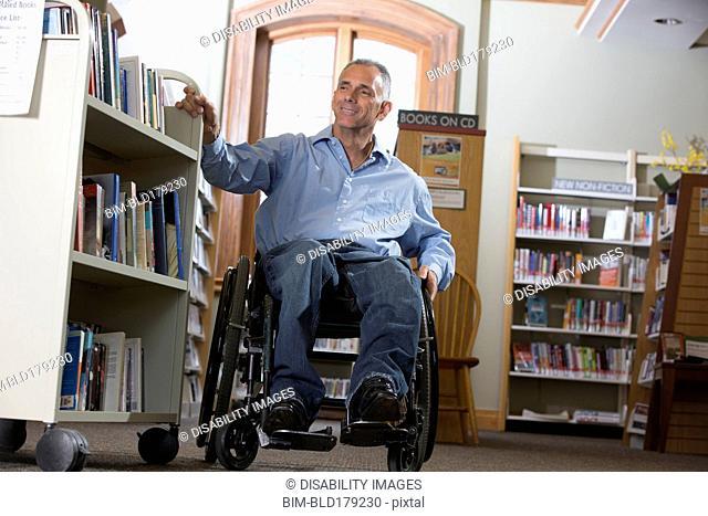 Caucasian man choosing book in library