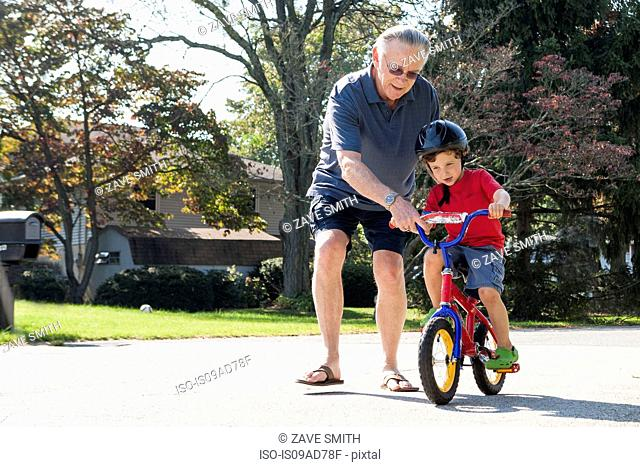 Grandfather encouraging young boy to ride bicycle