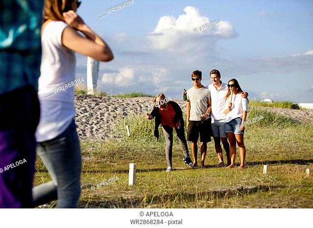 Happy young friends playing kubb game on field with Turning Torso in background