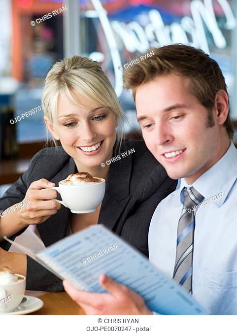 Businessman and businesswoman with lattes looking at cafe menu