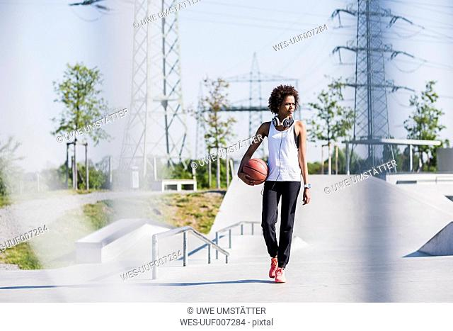Young woman with basketball in skatepark