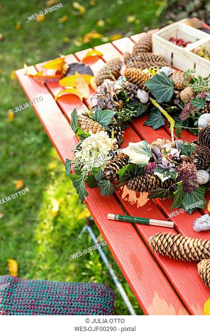 Autumnal wreath with hortensia, pine cones and ivy on garden table