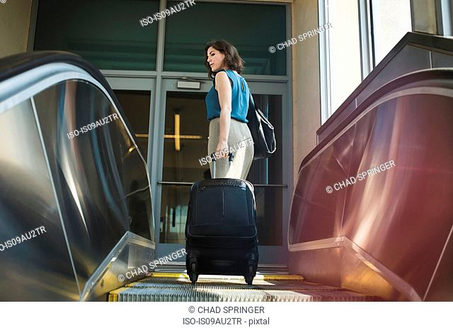Mid adult woman using escalator, holding wheeled suitcase, rear view